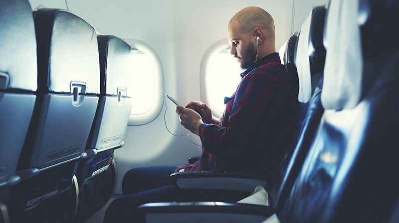 Man listening to music on his phone, on an airplane